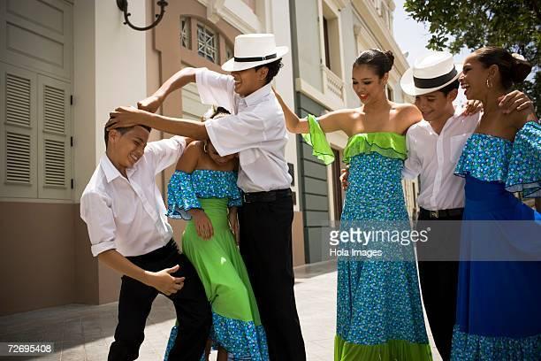 Boys in traditional Plena attire joking around, outdoors