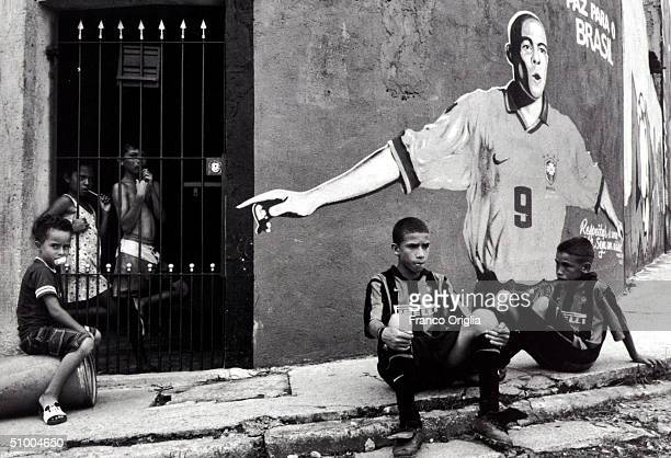 Boys involved with Inter Campus Project rest in front at a mural of Brazilian footballer Ronaldo in the slums of Santo Andre April 18 1999 in Sao...