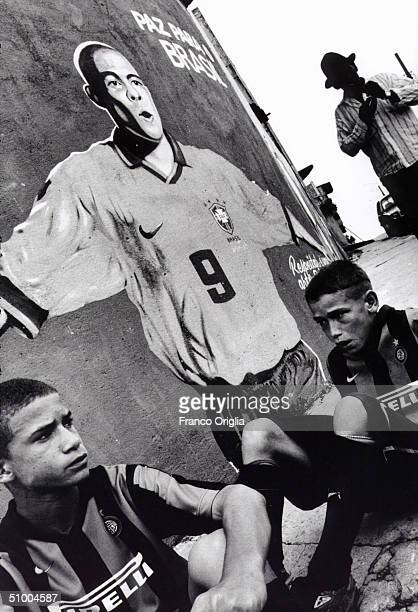 Boys involved with Inter Campus Project sit in front of a mural of Brazilian footballer Ronaldo in the slums of Santo Andre April 18 1999 in Sao...