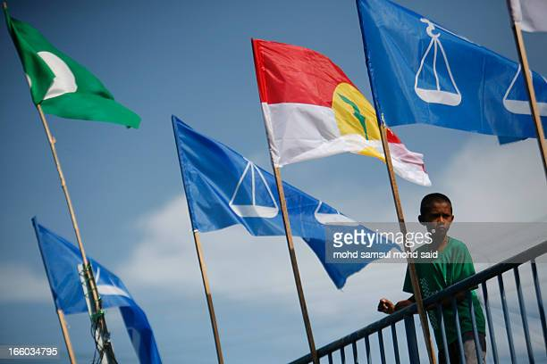 CONTENT] Boys is seen sit on the bridge bicycles as Malaysia flags of parties politcs is seen near him in Tumpat April 3 2013 Malaysian Prime...