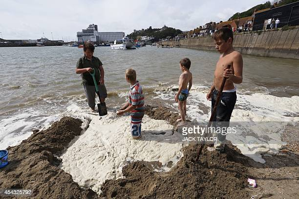 Boys join treasure hunters on a beach in Folkestone southeast England on August 29 2014 searching for gold bullion buried there by German artist...