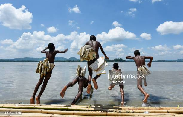 Boys jump in the Brahmaputra river wearing polystyrene sheets to keep themself afloat in the water during a hot summer day, in Guwahati, Assam, India...