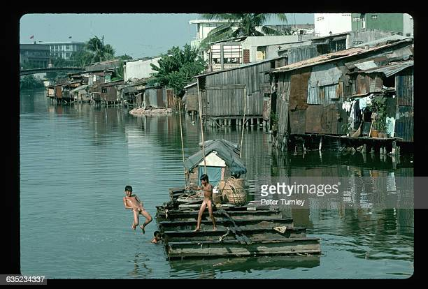 Boys jump into a river from a dock in a riverside slum outside of Ho Chi Minh City | Location near Ho Chi Minh City Vietnam