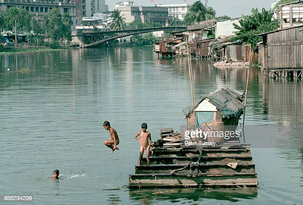 Boys jump into a river from a dock in a waterside slum outside of Ho Chi Minh City | Location near Ho Chi Minh City Vietnam