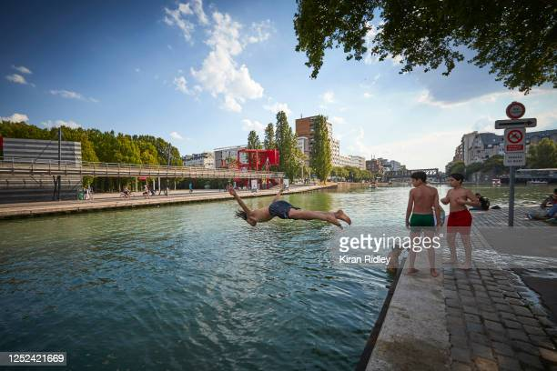 Boys jump into the canal at La Villette to cool off as temperatures in Paris reach 34°C with France experiencing a mini heatwave on June 25, 2020 in...