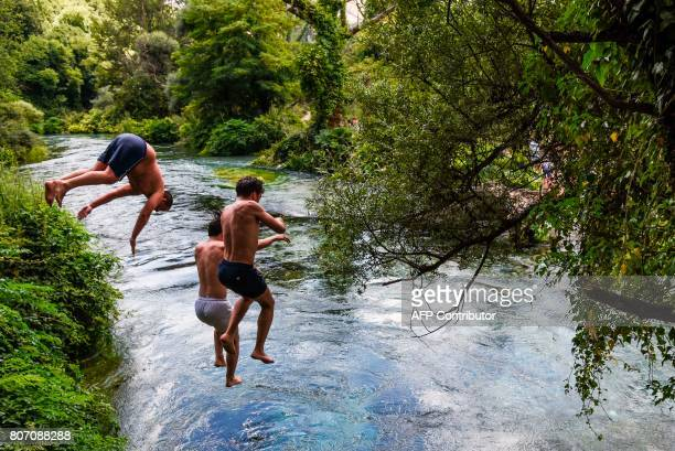 Boys jump to cool off in the Blue Eye river a water spring and natural phenomenon occurring near the Delvine district in Albania on July 4 2017 The...