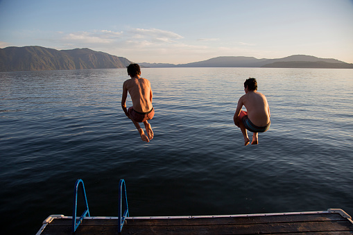 Boys jumping into lake from dock - gettyimageskorea