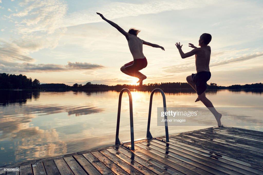 Boys jumping into lake : Foto de stock