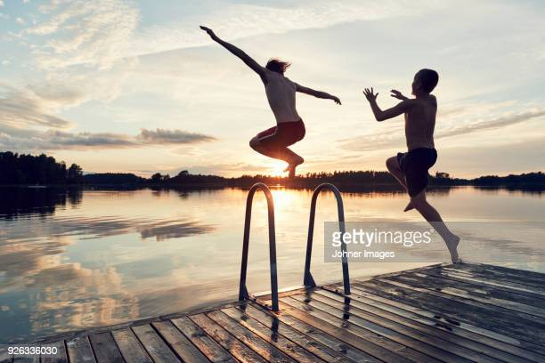 boys jumping into lake - sunset lake stock photos and pictures