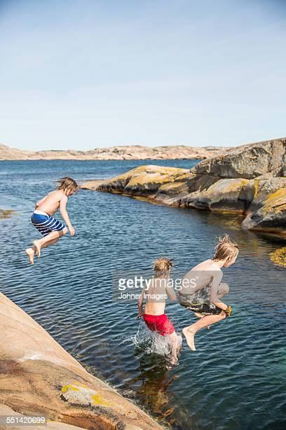 Boys jumping into sea
