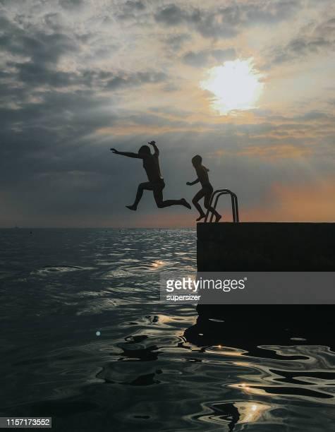jongens springen in de zee - pier stockfoto's en -beelden