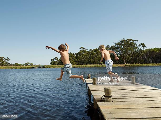 2 boys jumping into the water from a jetty