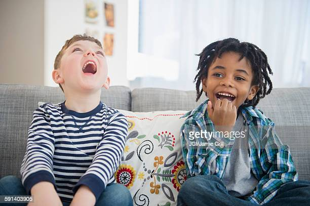 Boys laughing on living room sofa