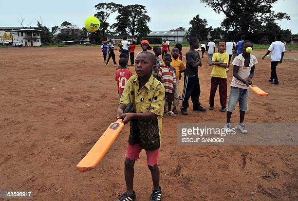 Boys learn to play cricket on November 15 2012 in Freetown at Kingtom Oval Sierra Leone's only cricket oval Packed with hard red dirt overlooked by a...