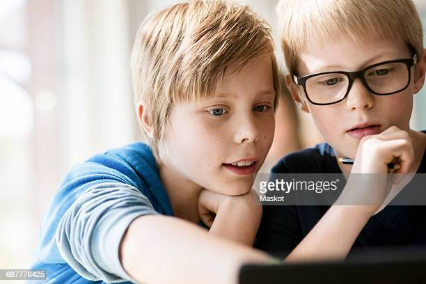 Boys learning from digital tablet in classroom