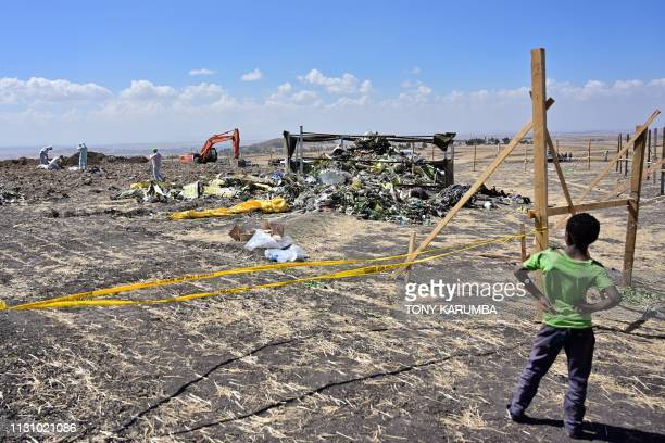 TOPSHOT A boys look as forensic investigators comb the ground for DNA evidence near a pile of twisted airplane debris at the crash site of an...