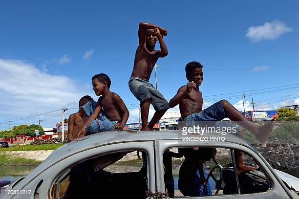 Boys look at friends playing football from an abandoned Volkswagen Beetle in a shantytown of Olinda about 18 km from Recife in northeastern Brazil on...