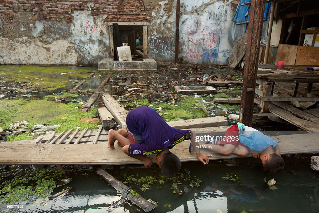 Boys look for snakes in the standing water in an abandoned factory in which there is a small community living November 24, 2015 in Jakarta, Indonesia. Jakarta, Southeast Asia's largest city is sinking slowly into the sea, largely due to overconsumption of ground water. Experts say that if nothing is done, the city's northern coast will be inundated with 5-7 meters (15-21 ft.) of seawater by the year 2080. The city has begun shoring up its sea defenses as increasing floods and severe storms due to rising temperatures and climate change threaten the mostly poor residents of Jakarta's northern coast with the loss of their homes.