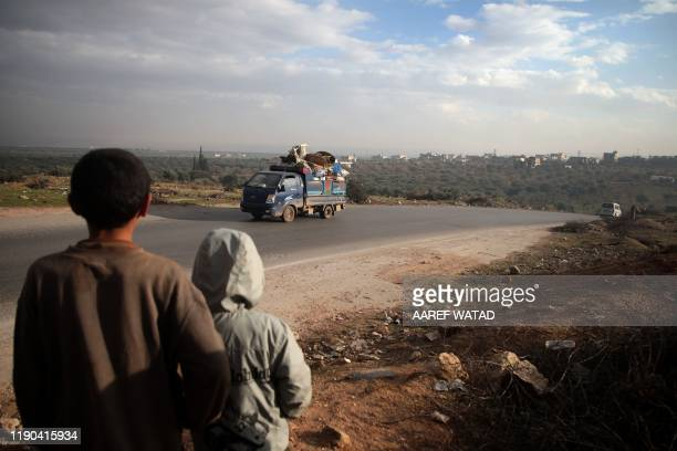 Boys look on at a truck loaded with furniture and belongings as in the village of al-Mastumah, about seven kilometres south of the city of Idlib on...