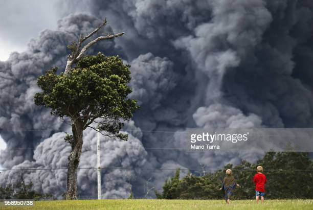 Boys look on while playing at a golf course as an ash plume rises in the distance from the Kilauea volcano on Hawaii's Big Island on May 15 2018 in...