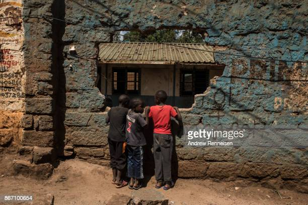 Boys look through a hole in a wall created yesterday outside of a polling station in the Kibera slum on October 27 2017 in Nairobi Kenya Tensions...