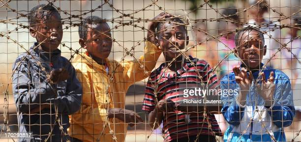 Boys look through the fence of Credo Mutwa park in Soweto Crime is ubiquitous in South Africa as are fences and razor wire Soweto is a large black...