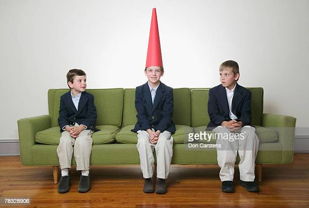 Boys looking at boy with dunce cap