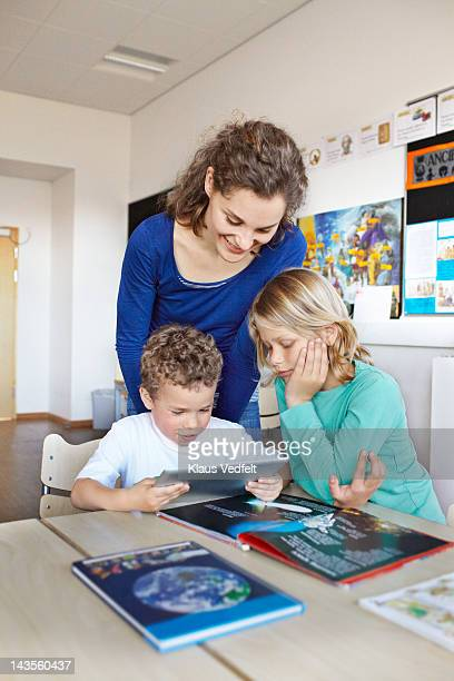 2 boys looking at tablet with teacher - teacher bending over stock photos and pictures