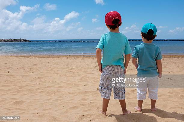 Boys looking at the sea in the beach
