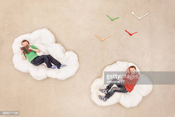 Boys lying on clouds reading and sleeping