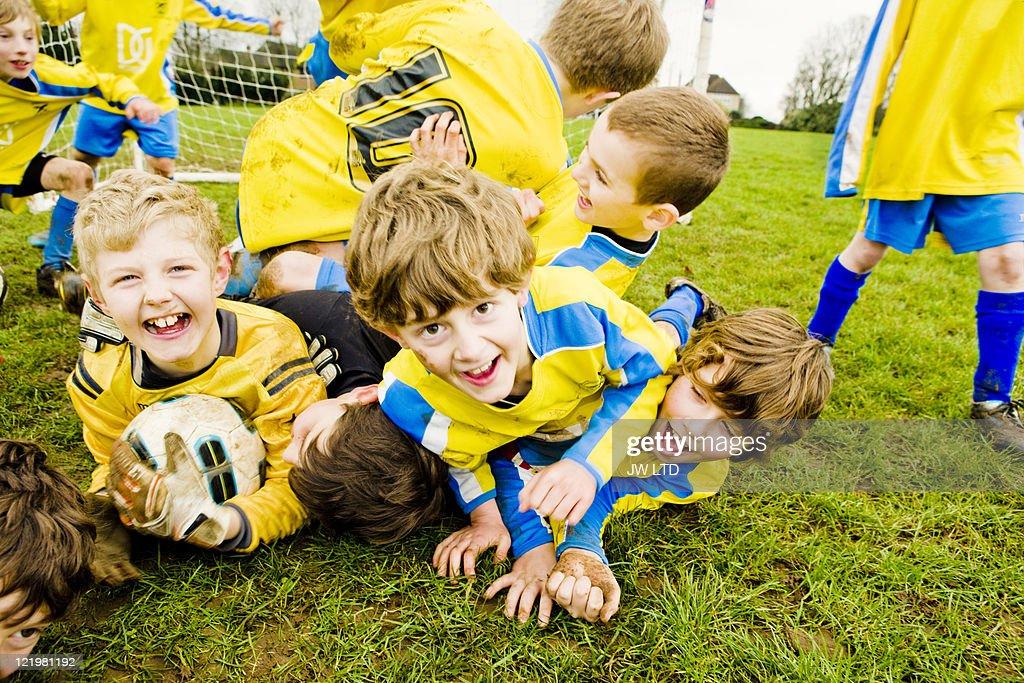 Boys lying on grass with football : Stock Photo