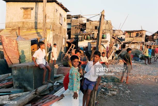 Boys milling around outside their homes in the slum with rubbish strewn around, Mumbai, India, February 2003