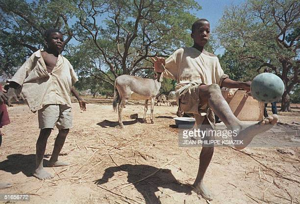 Boys of a village in Burkina Faso near the capital of Ougadougou play football 19 February as the country waits for the reprisal of the 21st African...