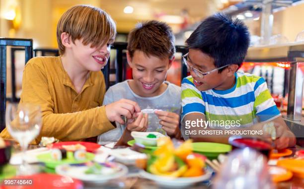 3 boys of diverse ethnicities enjoying all you can eat asian food in running sushi restaurant