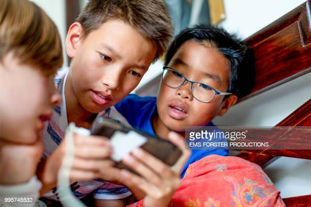 3 boys of diverse ethnicities gaming with smartphone
