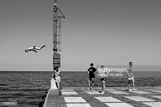 CONTENT] Boys of Lipari intent to dive from the pier of Canneto It reminds me of a scene in Italy 60s