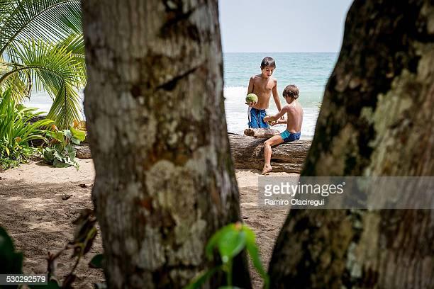 Boys on a beach with a coconut