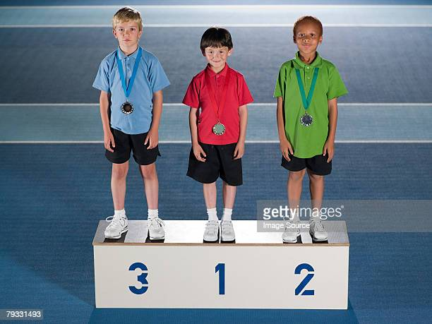 jungen auf einem podest - winners podium stock-fotos und bilder