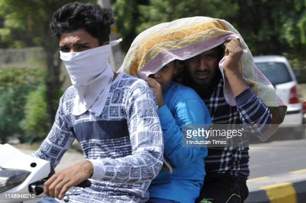 Boys on a two-wheeler cover themselves with a cloth to beat the heat on a summer day on June 10, 2019 in Noida, India. The mercury shattered all...