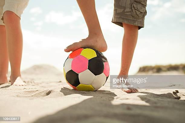 Niños en la playa con de fútbol