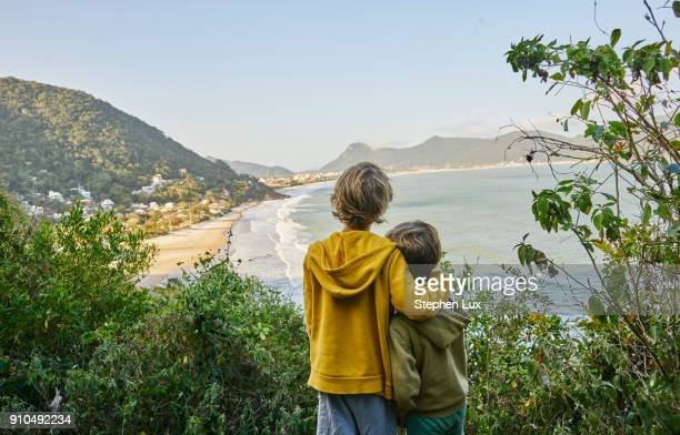 Boys on cliff looking away at beach, Florianopolis, Santa Catarina, Brazil, South America