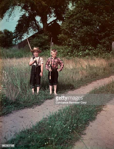 boys on dirt road with fishing poles - constance bannister stock photos and pictures