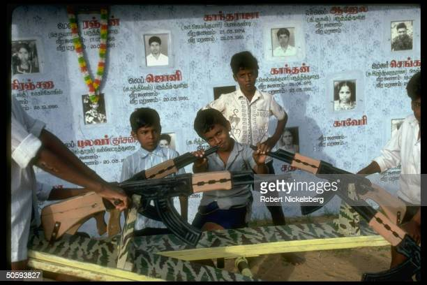 Boys on miltheme seesaws framed by pics birth/death dates of prob young victims of LTTE Tamil Tiger secessionist war at playground in Batticaloa Sri...