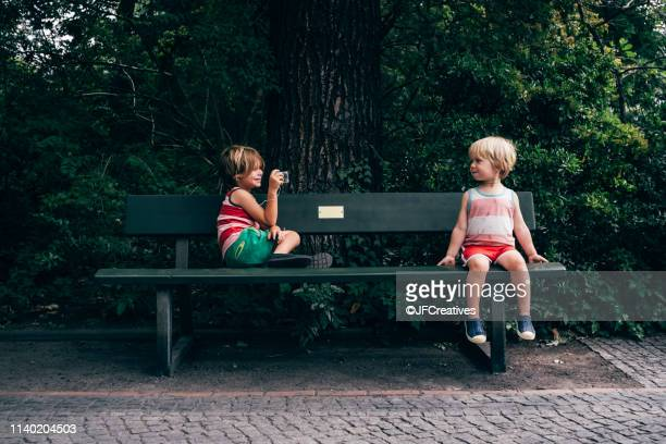 boys on park bench using digital camera to take photograph - bench stock pictures, royalty-free photos & images