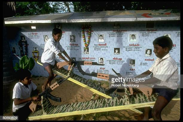 Boys on wartheme seesaws w bkgrd birth/deathdated pics of secessionist Tamil Tiger LTTE cadre battledead Point Pedro Jaffna peninsula Sri Lanka