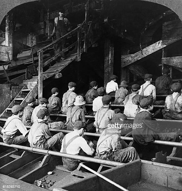 Boys pick slate in a coal breaker at an anthracite mine in Pennsylvania They sit in rows and are watched from above by a man