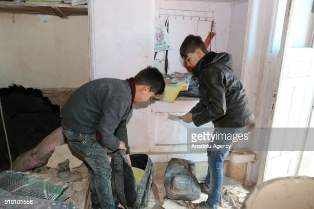 Boys pick up their belongings at their damaged house after a rocket fired by PYD/PKK terrorists from Syria's Afrin hit a house belonging to a Syrian...