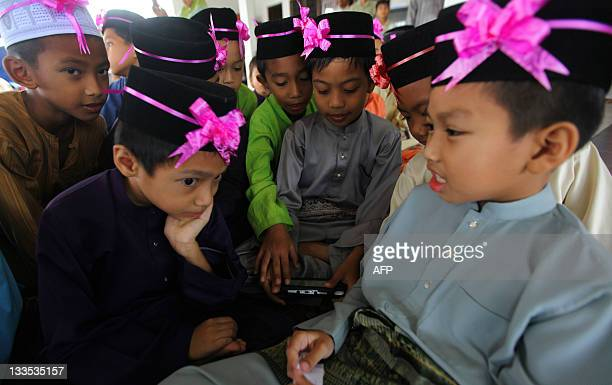 Boys play a console game before a mass circumcision ceremony in Kajang outside Kuala Lumpur on November 20 2011 About 30 boys aged between 7 and 11...