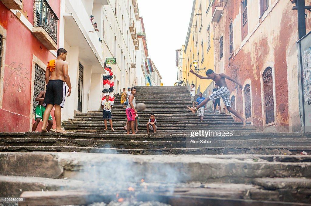 boys play a game of football on a street in sao luis brazil sao