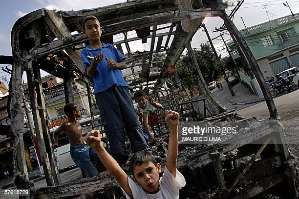 Boys play around an attacked bus burned with molotov cocktails by gang members in Campo Limpo neighborhood a south area of Sao Paulo Brazil 15 May...